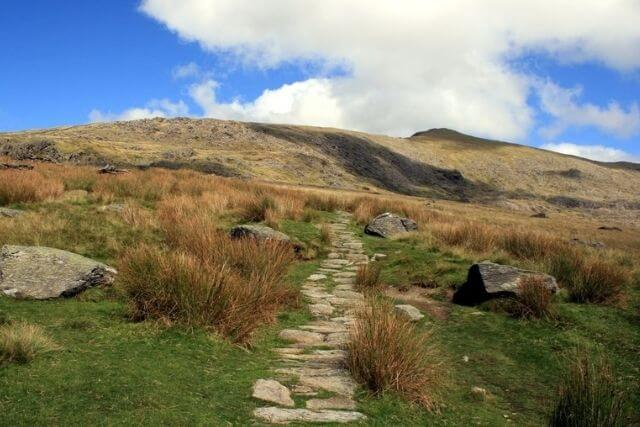 Snowdon path with green grass and hills in the background