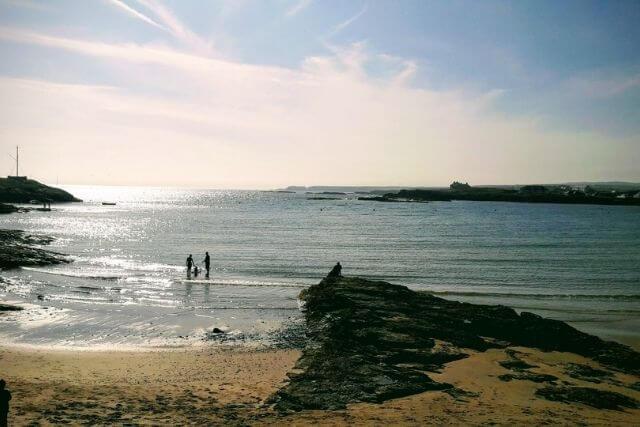 People walking along the beach at Trearddur Bay